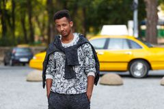 Portrait of a cheerful young man in casual clothes, outside, doing face grimace, isolated on blurred street background. stock image