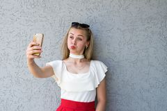 Funny blonde posing with smartphone Stock Images