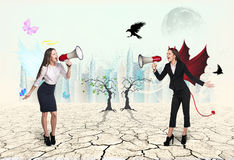 Portrait of angel and devil girls with megaphone Stock Photography