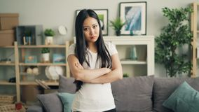 Portrait of angry Asian lady looking at camera, frowning and shaking her head expressing disappointment and disapproval
