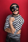 Portrait of a angry bandit threaten with a fist. On red background Stock Photo