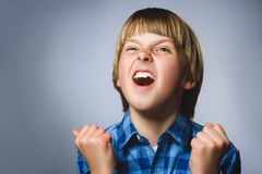 Portrait of angry boy in blue shirt with hands up yelling on gray studio background. Negative human emotion. Facial expression. Closeup stock image