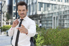 Portrait of angry businessman pointing at you outside office building Royalty Free Stock Image