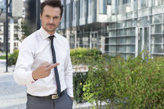 Portrait of angry businessman showing middle finger outside office building Stock Photos