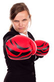 Portrait of angry businesswoman with boxing gloves punching Stock Photography