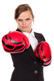 Portrait of angry businesswoman with boxing gloves punching Royalty Free Stock Images