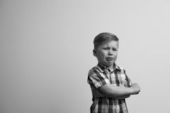 Portrait of angry child looking at camera. Unhappy crying caucasian boy staying with arms crossed on chest and looking at camera. Emotional portrait of little royalty free stock photography