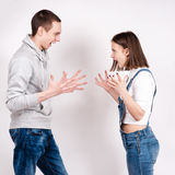 Portrait of an angry couple shouting each other against white background Stock Photos