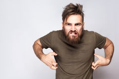 Portrait of angry crazy bearded man with dark green t shirt against light gray background. Stock Photography