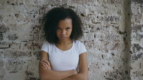 Portrait of angry curly mixed race woman looking into camera nervous on brick wall background