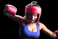 Portrait of angry female boxer with fighting stance. Against black background stock photos