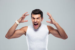 Portrait of angry fitness man shouting. Over gray background Royalty Free Stock Photo