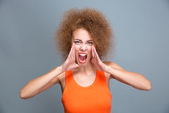Portrait of angry furious young curly screaming woman Stock Images