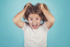 Portrait of angry girl. On blue background royalty free stock photo