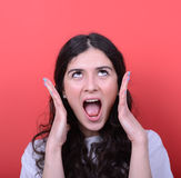 Portrait of angry girl screaming against red background Stock Photography