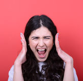 Portrait of angry girl screaming against red background Royalty Free Stock Photo