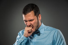 Portrait of an angry guy biting his fist. Human emotion. Stock Photo