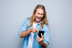 Portrait of angry guy screaming pointing with forefinger to mobi. Lephone standing over grey background Royalty Free Stock Image