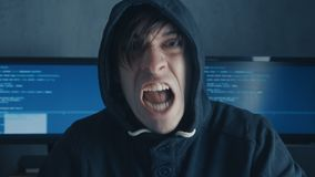 Portrait of Angry Hacker Programmer screams and shows aggression while working at the computer. Stress in the workplace.