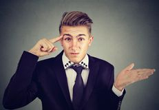 Portrait of angry mad young man gesturing with finger asking are you crazy?. Isolated on gray background. Negative emotions feeling body language Royalty Free Stock Photography