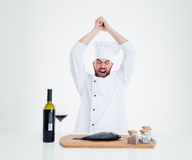 Portrait of angry male chef cook cutting fish Stock Images