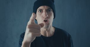 Portrait of angry man in black cap screaming with agression. Threat of violence.