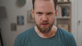 Portrait of angry man displeased and fearful doing disgust face because aversion reaction, annoyance guy sitting on a. Portrait of angry man looking into camera stock video footage