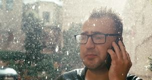 Portrait of the angry man with eyeglasses shouting at somebody while talking on the mobile phone in rain. 4k footage.