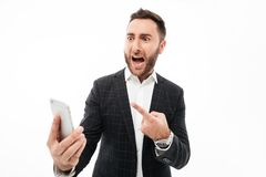 Portrait of an angry man holding mobile phone Royalty Free Stock Photography