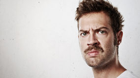 Portrait of an angry man with mustache. Portrait of a young angry man on bright concrete background stock photos
