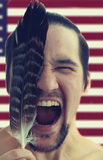 Portrait of angry man screaming with feather and eyes closed on USA flag background. Royalty Free Stock Images