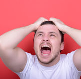 Portrait of angry man screaming and pulling hair against red bac. This image is made in studio with model standing against colored backgrounds.Set of various Royalty Free Stock Images