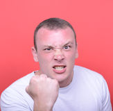 Portrait of angry man screaming showing fist against red backgro Stock Image