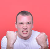 Portrait of angry man screaming showing fist against red backgro Stock Photos