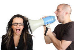 Portrait of angry man shouting at megaphone. Portrait of angry man shouting at his secretary through megaphone who is indifferent to it Royalty Free Stock Photos
