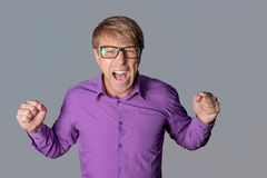 Portrait of a angry man with glasses staring at camera, shows finger and shouting over gray background royalty free stock images