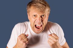 Portrait of a angry man in white tshirt holding fists on blue background royalty free stock image