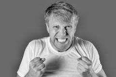 Portrait of a angry man in white tshirt holding fists on blue background. Monochrome photography royalty free stock image