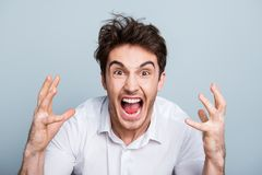 Portrait of angry overworked tired director screaming in rage be. Cause of having no time to finish his project, gesturing with arms over gray background Royalty Free Stock Image