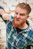 Portrait of angry red haired hipster man with blue plaid shirt Royalty Free Stock Images