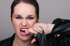 Portrait of angry rocker girl in close-up view. As rebel lifestyle concept on gray background Stock Photos