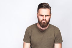 Portrait of angry sad bearded man with dark green t shirt against light gray background. Stock Photography