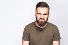 Portrait of angry sad bearded man with dark green t shirt against light gray background. Royalty Free Stock Image