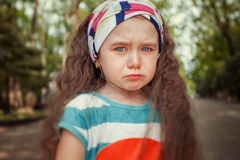 Portrait of angry and sad little girl. Children`s emotions. Portrait of angry and sad little girl outdoor. Children`s emotions Royalty Free Stock Photography