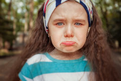 Portrait of angry and sad little girl. Children`s emotions. Portrait of angry and sad little girl outdoor. Pouted her lips. Children`s emotions Stock Photos