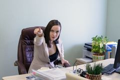Portrait of angry, screaming young business woman in a leather chair behind the office Desk Stock Photos