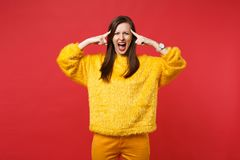 Portrait of angry screaming young woman in yellow fur sweater pointing fingers on temple, head isolated on red wall. Background in studio. People sincere stock image