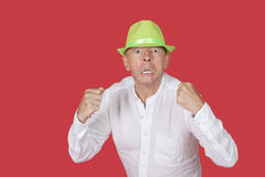 Portrait of an angry senior man clenching fists against red background Stock Photo