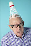 Portrait of angry senior man with shuttlecock on head over colored background Stock Image