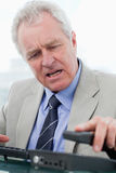 Portrait of an angry senior manager hanging up Royalty Free Stock Photography